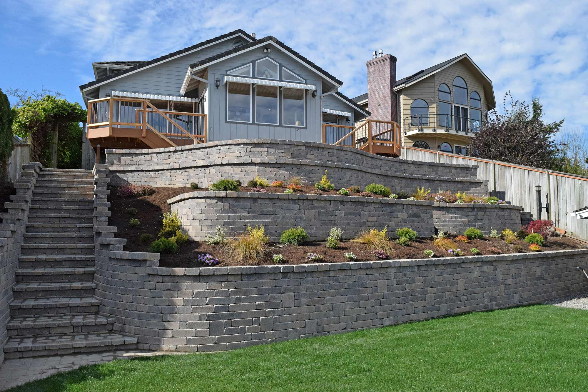 This Massive, 4 Tier Retaining Wall Includes An Integrated Stairway,  Landscaping And A Paver Patio Above The Top Tier.
